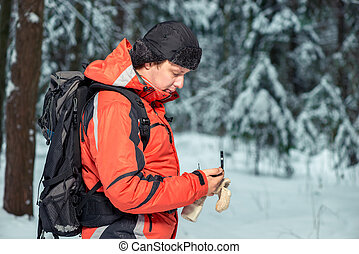 tourist with a compass and a backpack got lost in the winter forest