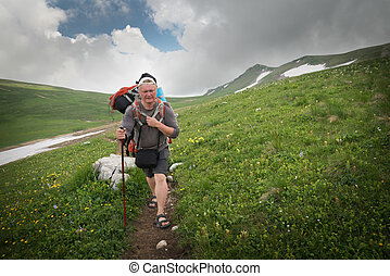 Tourist with a large backpack on a pathway in the mountains