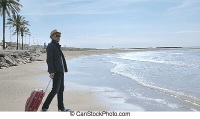Tourist in a hat and with a suitcase came to the seashore, vacation concept