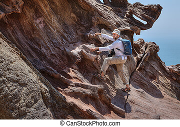 Tourist with backpack climbs on a rock to take pictures.