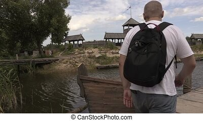 Tourist with backpack near old boat