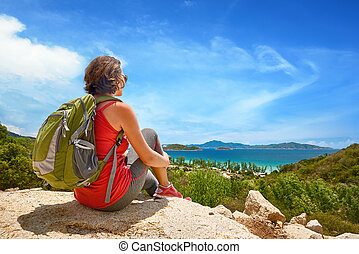 Tourist with backpack relaxing on top of the mountain and...