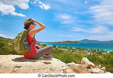 Tourist with backpack sit on a rock on clear sky background, looking at beautiful landscape