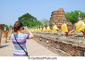 Tourist with camera in front of budha statues