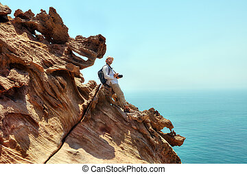 Tourist with camera sits on the edge of a cliff.