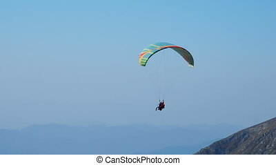 Tourist with instructor hovering in the sky on a paraglider....