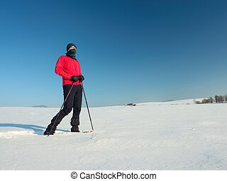 Tourist with snowshoes walk in snowy drift. Sunny freeze...