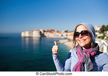 Tourist woman against Dubrovnik old town giving the thumbs up