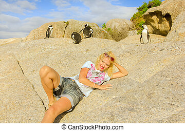Cape Town in Western Cape, South Africa. Happy blonde caucasian tourist woman on the rocks of Boulder Beach in summer, popular for an African penguins colony.