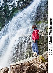 Tourist woman at waterfall Svandalsfossen, Norway