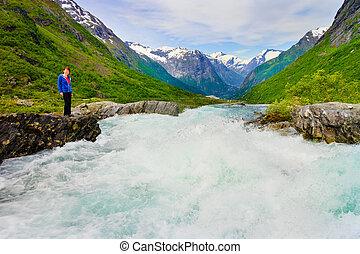 Tourist woman by Videfossen Waterfall in Norway