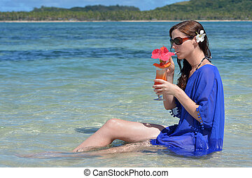 Tourist woman drinks a tropical cocktail in the waters of a resort on an island in Fiji