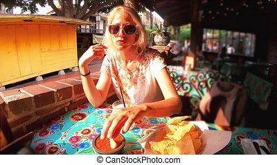 Tourist woman eating Nachos chips - SLOW MOTION: El Pueblo...
