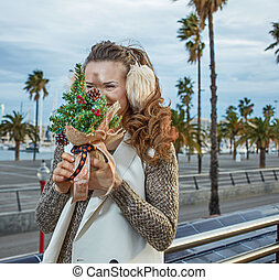 tourist woman in Barcelona hiding behind a little Christmas tree