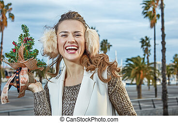 tourist woman in Barcelona showing a little Christmas tree