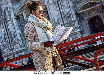 tourist woman in front of Duomo in Milan, Italy looking at map