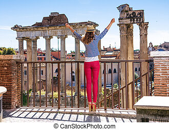 tourist woman in front of Roman Forum in Rome, Italy rejoicing