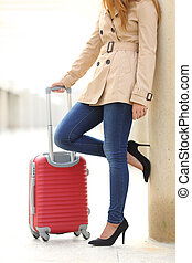 Tourist woman legs waiting with a suitcase in an airport