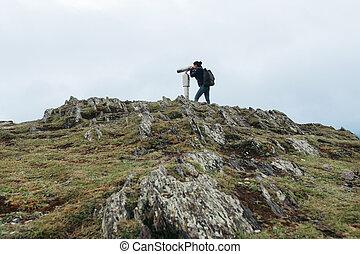 tourist woman looking at binoculars on a hillside