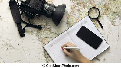 Tourist woman looking at world map planning travel adventure. top view