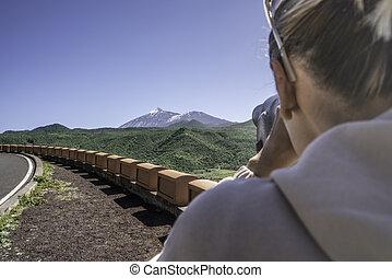 Tourist woman looking through binoculars at volcano