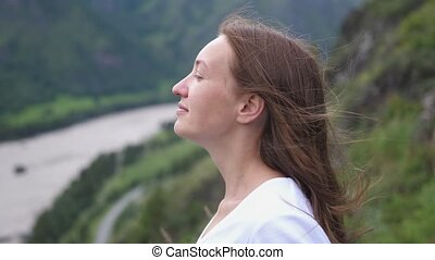 Tourist woman meditate or dream on top of the mountain with flying hair. slow motion
