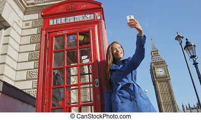 Tourist woman taking selfie photo using mobile smart phone by red telephone booth in London, England, Great Britain. Happy young female urban professional by Big Ben enjoying leisure time in UK.