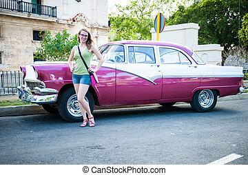 Tourist woman posing next to traditional cuban car, retro american oldtimer.