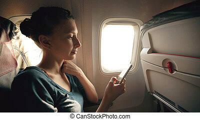 Tourist woman sitting near airplane window at sunset and using mobile phone during flight