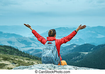 tourist woman sitting on the cliff in the mountains