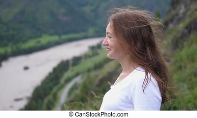 Tourist woman smiling on top of the mountain with flying hair. slow motion