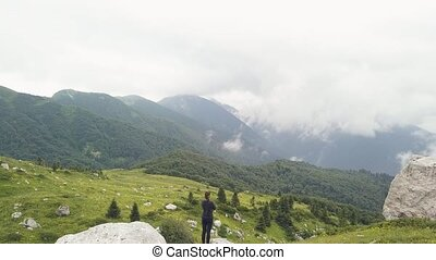 Tourist woman standing on mountain edge and watching on...