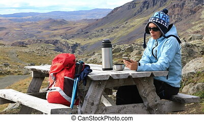 Tourist woman using the cell phone - Tourist woman sitting...