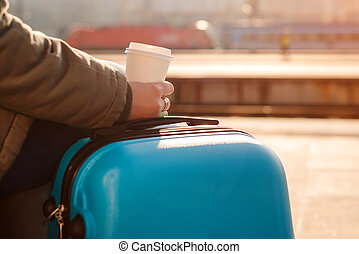 Tourist woman waiting for train. Woman with suitcase. Female holding cup of coffee at railway station.