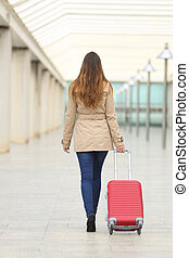 Tourist woman walking carrying a suit case in an airport