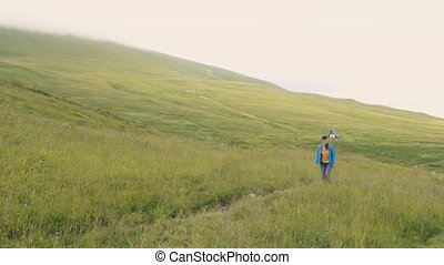 Tourist woman walking on green meadow on mountains and hills...