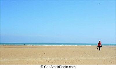 Tourist woman walking on the beach