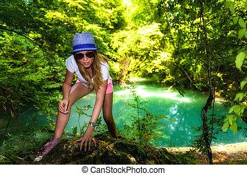tourist woman walking through the woods along a river