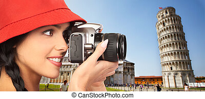 Tourist woman with a camera. Pisa tower.