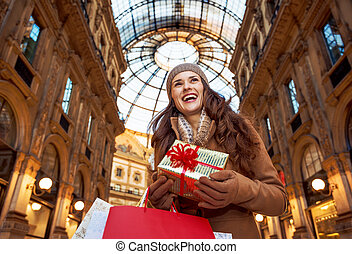 tourist woman with Christmas gift in Milan looking into distance