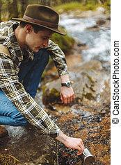 touriste, homme, jeune, rivière, tasse, tenue, remplissage, cup., beau, water.
