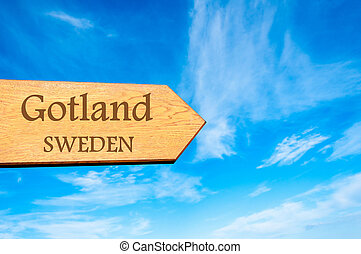 Wooden arrow sign pointing destination GOTLAND, SWEDEN against clear blue sky with copy space available. Travel destination conceptual image