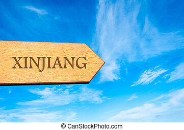 Wooden arrow sign pointing destination XINJIANG, CHINA against clear blue sky with copy space available. Travel destination conceptual image
