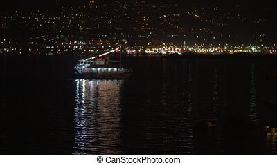 Touristic ship sailing along night city - Small illuminated ...