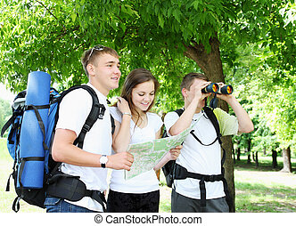 Tourists - A group of young backpackers with map and...