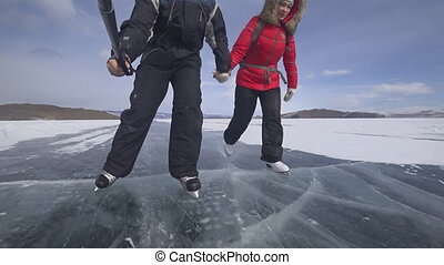 Tourists and travelers on the ice of Lake Baikal skate.