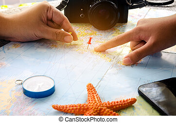 Tourists are planning a trip on a map and mark a place of...