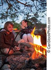 Tourists around the campfire at night.