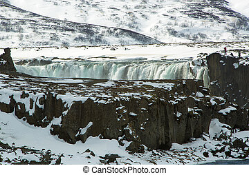 Tourists at the Icelandic waterfall Godafoss in wintertime