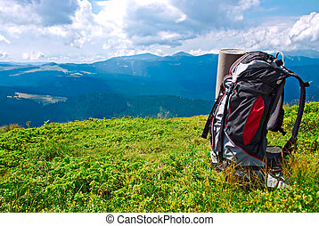 Tourists backpack in mountains over evening sky